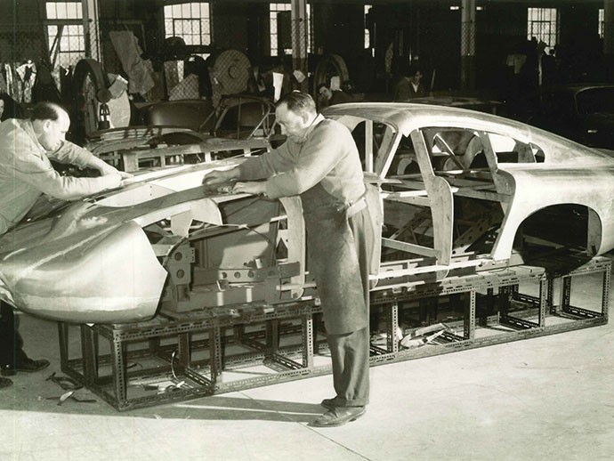 Master sheet metal worker Bert Brookes, in apron, affixes the magnesium/aluminum alloy panels to DP215 in 1963 (Credit - Courtesy of Ted Cutting/Aston Martin Lagonda).