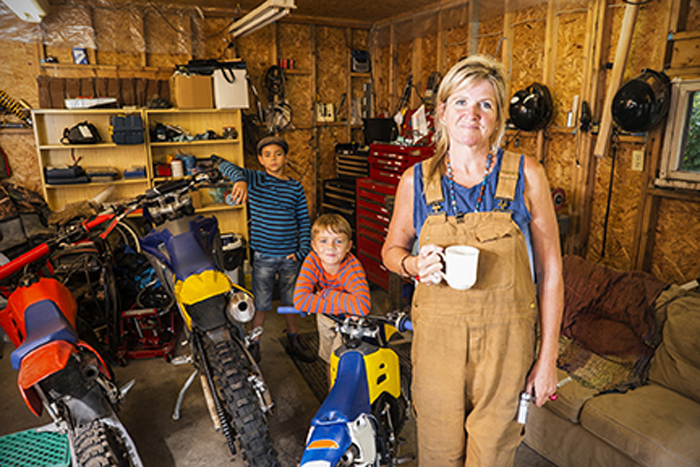 A middle-aged, Caucasian mother in overalls stands in a garage full of motorcycles and dirt bikes with her two sons.  An authentic scene at home with a real family.