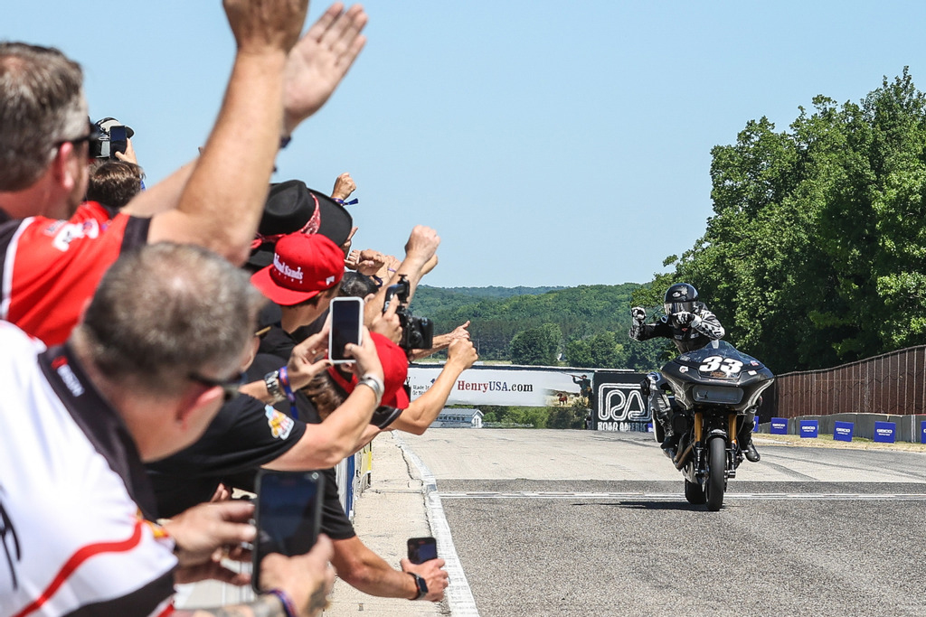 Kyle Wyman (#33) salutes the Harley-Davidson Screamin' Eagle crew of factory engineers as he takes the checkered flag in the MotoAmerica King of the Baggers race at Road America. Photo Credit: Brian J. Nelson